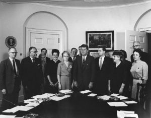 President John F. Kennedy with Members of the Consumer Advisory Council, 1962. Dr Persia Campbell stands beside President Kennedy. Photograph by Abbie Rowe. White House Photographs. John F. Kennedy Presidential Library and Museum, Boston.