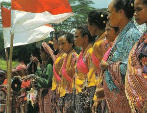 """The Timorese with their national flag, red and white,"" in East Timor in Pictures (1984). Image via the Department of Foreign Affairs, Republic of Indonesia."